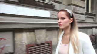 Beautiful young woman walking down the street