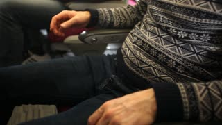BELGRADE, SERBIA - FEBRUARY 2014: View of a man fastening his seat belt. Safe travel is of great importance while traveling in airplane.