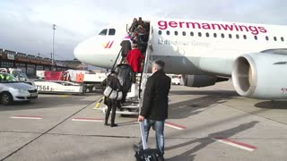 BERLIN, GERMANY - 28 JANUARY 2015: Passengers climbing on the stairs and entering into the airplane at the Tegel Airport.