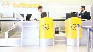 BERLIN, GERMANY - 28 JANUARY 2015: Two airport employees at Lufthansa check-in desk at Tegel Airport in Berlin, Germany.
