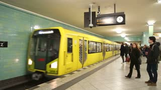BERLIN, GERMANY - 28 JANUARY 2015: Underground railway U-bahn train coming into station and commuters entering the train.