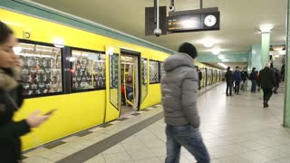 BERLIN, GERMANY - 28 JANUARY 2015: Yellow underground railway U-bahn stopped at station waiting for passengers to get in and doors finally close.