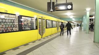 BERLIN, GERMANY - 28 JANUARY 2015: Yellow underground railway U-bahn train leaving station and camera follows the train into tunnel.
