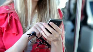 Blond girl sitting in tram, close up on mobile, phone, cell, holding glasses