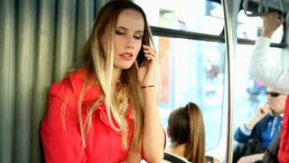 Blond woman, standing in tram and talking on her phone