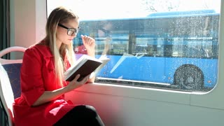 Blond young woman sitting in tram, reading book