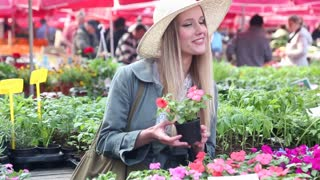 Blonde beautiful woman holding flower in the market