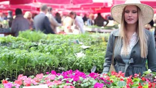 Blonde beautiful woman smelling flowers in the market
