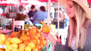 Blonde girl at the market picking fruit