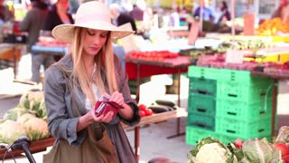 Blonde girl is putting away her money at the market