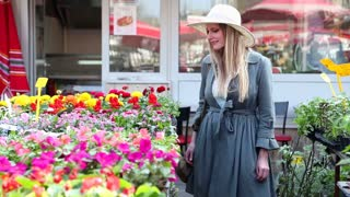 Blonde girl looking and smelling flowers in the market