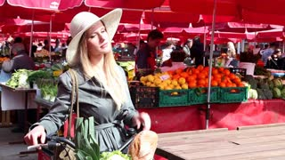 Blonde girl with bike standing at the market, smiling