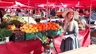 Blonde girl with bike standing at the market