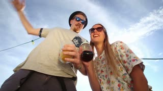 Blonde woman and male hipster looking down at camera and crazy dancing