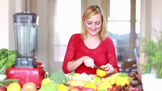 Blonde Woman cutting orange for fruit shake, in slow motion, graded