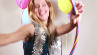 Blonde woman dancing with hula hoop in photo booth