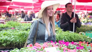 Blonde woman is smelling flowers in the market