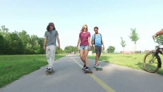 Blonde woman longboarding with friends