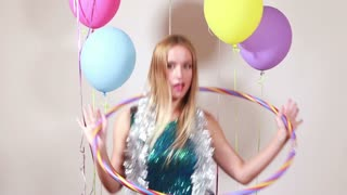 Blonde woman playing with hula hoop in photo booth