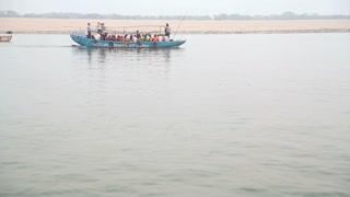 Blue boat full of people sailing through river Ganges in Varanasi.