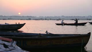 Boat sailing through river Ganges at sunset.