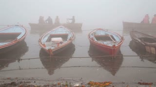 Boats tied to a dock of Ganges and boats sailing in background.
