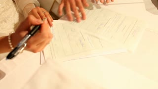 Bride signing her name on wedding prenuptial agreement at church