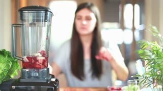 Brunette woman blending fruits in blender, in slow motion, graded
