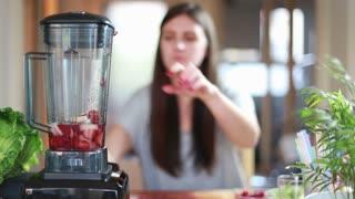 Brunette woman blending fruits in blender