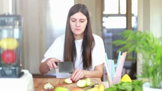 Brunette woman chopping apple on wooden board for fruit shake, graded