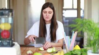 Brunette woman chopping apple on wooden board for fruit shake