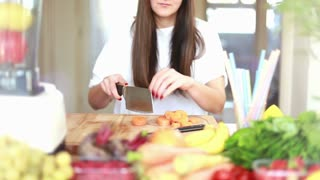 Brunette woman cutting carrot into pieces on wooden board for fruit shake, graded