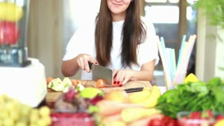 Brunette woman cutting carrot into slices on wooden board for fruit shake, graded