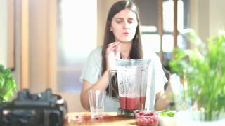 Brunette woman pouring fruit smoothie into glass, in slow motion, graded