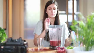 Brunette woman pouring fruit smoothie into glass, in slow motion