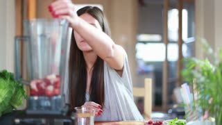 Brunette woman pouring water into blender with fruits, in slow motion