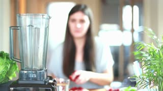Brunette woman putting fruits in blender for blending, graded