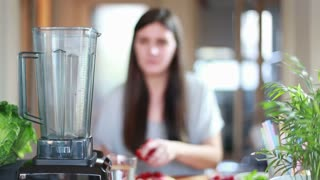 Brunette woman putting fruits in blender for blending