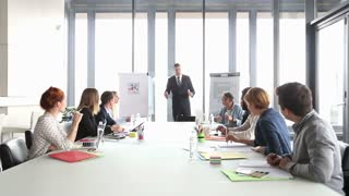 Business people applauding director during a meeting in conference room