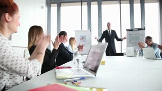 Business people clapping after meeting with manager in conference room