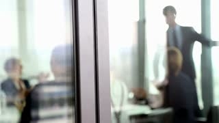 Business people clapping to colleague in conference room, behind glass wall, slow motion, graded