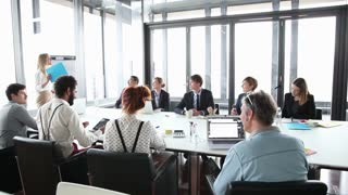 Business people sitting at table while beautiful female colleague giving presentation in conference room, slow motion