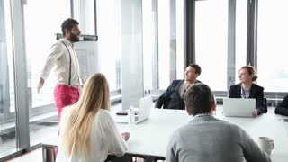 Business people sitting at table while handsome male colleague giving presentation in conference room
