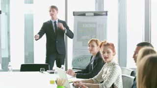 Business people talking during corporate presentation in conference room, graded