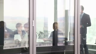 Businessman giving presentation in conference room behind glass wall