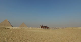 CAIRO, EGYPT - 04 FEBRUARY 2016: Woman riding horse with local man in front of Giza pyramids, Egypt