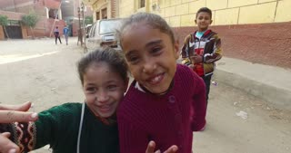 CAIRO, EGYPT - FEBRUARY 03, 2016: closeup of two local girls posing for camera, boy in background at Giza