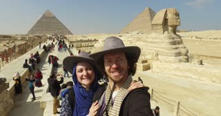 CAIRO, EGYPT - FEBRUARY 04, 2016: Tourist couple taking selfie at Giza pyramids complex