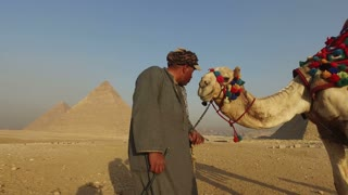 CAIRO, EGYPT - FEBRUARY 14, 2016: Local man kissing his camel in front of Giza pyramids