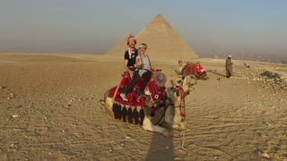 CAIRO, EGYPT - FEBRUARY 14, 2016: Smiling couple sitting on camel in front of Giza pyramids